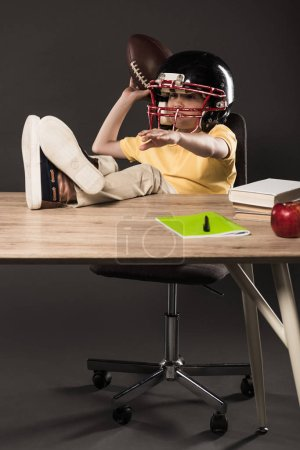smiling schoolboy in american football helmet holding ball and sitting with legs on table with books, apple and textbook on grey background