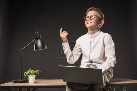smiling little boy in eyeglasses doing idea gesture by finger and using laptop while sitting on table with lamp and plant on grey background
