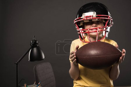 happy little boy in american football helmet holding ball on grey background