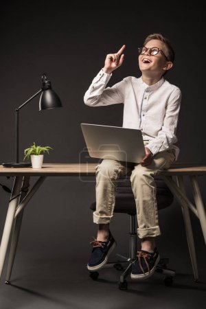 excited little boy in eyeglasses doing idea gesture by finger and using laptop while sitting on table with lamp and plant on grey background