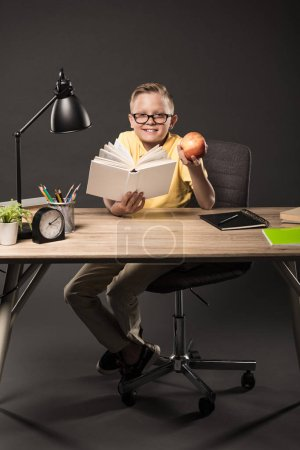 smiling schoolboy in eyeglasses holding apple and reading book at table with books, plant, lamp, colour pencils, clock and textbook on grey background