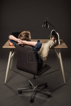rear view of little boy resting with legs on table with laptop, apple and lamp on grey background