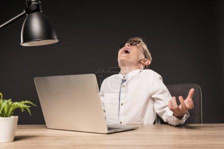 Photo pour Heureux petit garçon à lunettes gestuelle par mains et assis à table avec ordinateur portable, plante et lampe sur fond gris - image libre de droit