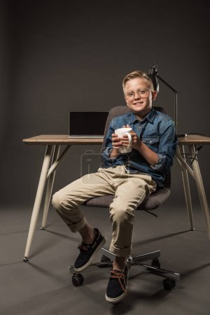 little boy in eyeglasses holding coffee cup and sitting on chair near table with laptop and lamp on grey background