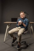 """Постер, картина, фотообои """"маленький мальчик в очки, держа чашку кофе и сидя на стуле возле таблицы с ноутбуком и лампа на сером фоне"""""""