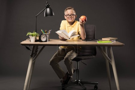 smiling schoolboy in eyeglasses holding apple and reading book at table with books, plant, lamp, colour pencils, apple, clock and textbook on grey background