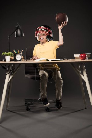 happy schoolboy in american football helmet holding ball and sitting at table with books, plant, lamp, colour pencils, apple, clock and textbook on grey background