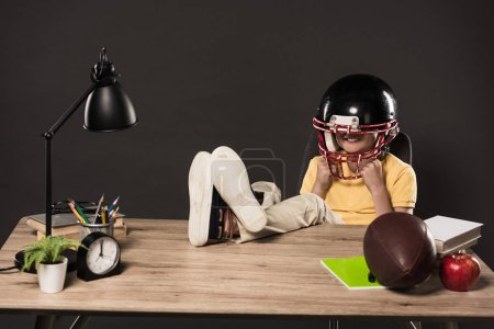 smiling schoolboy in american football helmet sitting with legs on table with ball, books, plant, lamp, colour pencils, apple, clock and textbook on grey background