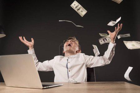excited little boy in eyeglasses throwing dollar banknotes at table with laptop and lamp on grey background