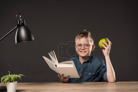 smiling schoolboy holding pear and reading book at table with plant and lamp on grey background