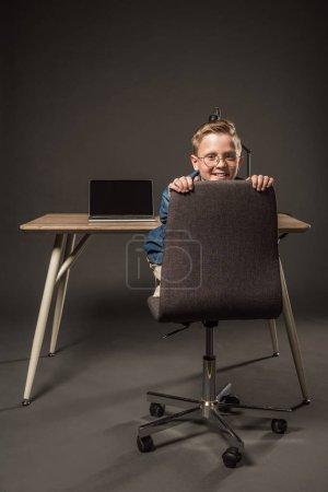 Foto de Niño sonriente en anteojos sentado en la silla junto a la mesa con ordenador portátil y lámpara en fondo gris - Imagen libre de derechos