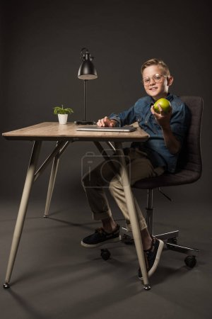 smiling little boy in eyeglasses holding pear and sitting at table with laptop, lamp and plant on grey background