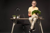 little schoolboy in eyeglasses holding apple and doing homework while sitting on table with books, plant, lamp, colour pencils, clock and textbook on grey background
