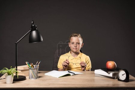 schoolboy holding eyeglasses and sitting at table with books, plant, lamp, colour pencils, apple, clock and textbook on grey background
