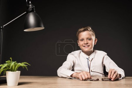 happy little boy sitting at table with eyeglasses, plant and lamp on grey background