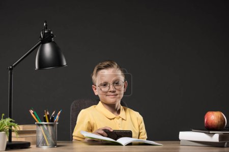 smiling schoolboy using smartphone at table with books, plant, lamp, colour pencils, apple, clock and textbook on grey background