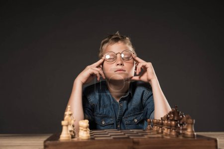 thoughtful little boy with closed eyes in eyeglasses holding fingers on temples at table with chess board on grey background