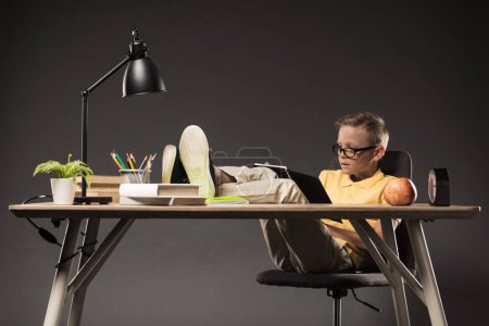 schoolboy in eyeglasses doing homework, holding apple and sitting with legs on table books, plant, lamp, colour pencils, clock and textbook on grey background