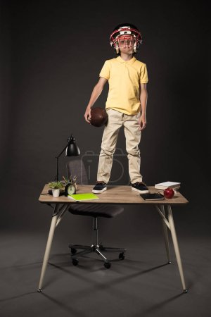 schoolboy in american football helmet holding ball and standing on table with books, plant, lamp, colour pencils, apple, clock and textbook on grey background