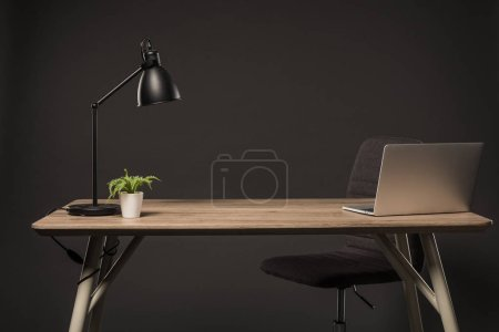 close up view of chair and table with lamp, plant, book and laptop on grey background