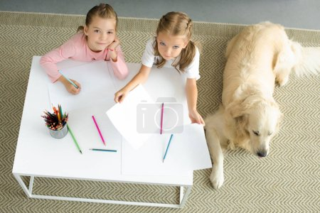 overhead view of little sisters drawing pictures at table with golden retriever dog resting on floor near by at home