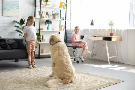 selective focus of little children playing with golden retriever dog at home