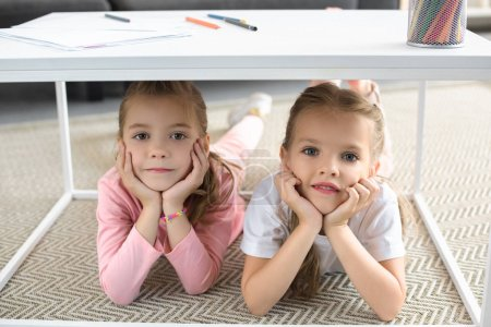 portrait of little sisters looking at camera while lying under table with pencils at home