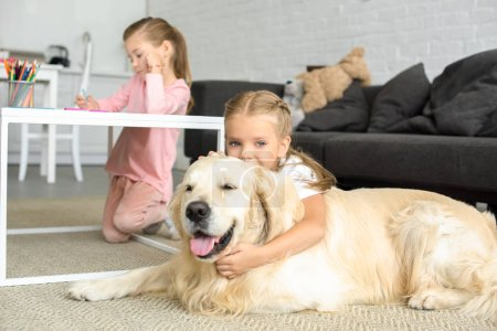 selective focus of kid hugging golden retriever dog on floor while sister drawing picture at home