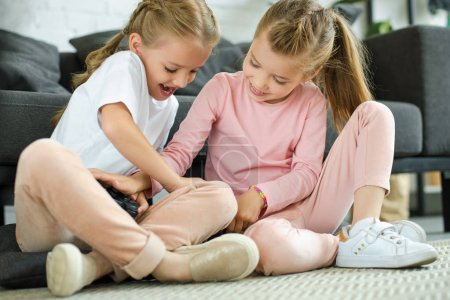 little sisters with gamepad going to play video game together at home
