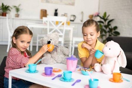 adorable little sisters pretending to have tea party together at home