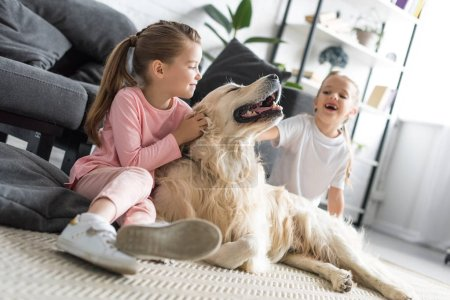 happy adorable kids petting golden retriever dog at home