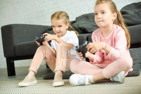 little sisters with gamepads playing video game together at home