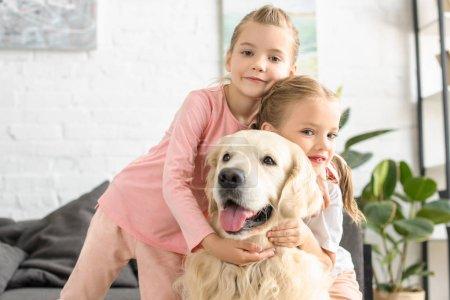 portrait of adorable kids hugging golden retriever dog at home