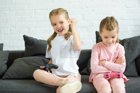 adorable little sisters with gamepads playing video game together at home
