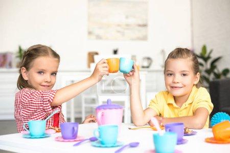 Foto de Lindos hermanitas tintineo de tazas de juguete mientras finge tener té juntos en casa - Imagen libre de derechos