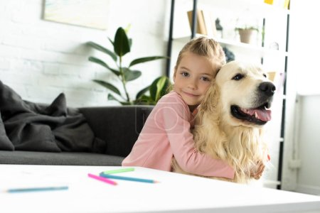 portrait of cute child hugging golden retriever dog near by at home