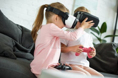 Photo for Obscured view of kids in virtual reality headsets playing video game on sofa at home - Royalty Free Image
