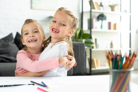 Photo for Portrait of happy little children hugging each other at table with papers and pencils for drawing at home - Royalty Free Image