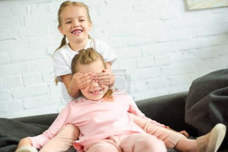 adorable little kid covering eyes to sister on sofa at home