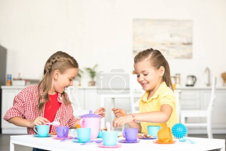 Photo for Cute little sisters pretending to have tea party together at home - Royalty Free Image