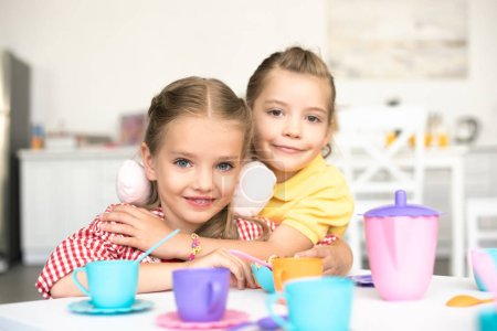 portrait of little smiling sisters pretending to have tea party together at home