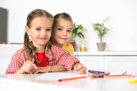 portrait of cute little children at table with papers and pencils for drawing at home