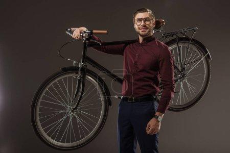 Photo pour Bel homme dans lunettes tenue cycliste et souriant à la caméra sur fond noir - image libre de droit
