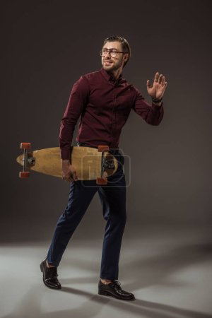 full length view of handsome smiling man in eyeglasses holding longboard and waving hand on black