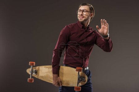 handsome smiling man in eyeglasses holding longboard and looking away isolated on black