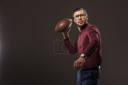serious man in eyeglasses throwing rugby ball and looking at camera isolated on black