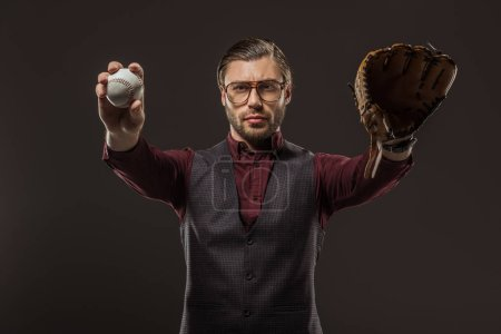 serious man in eyeglasses holding baseball ball and looking at camera isolated on black