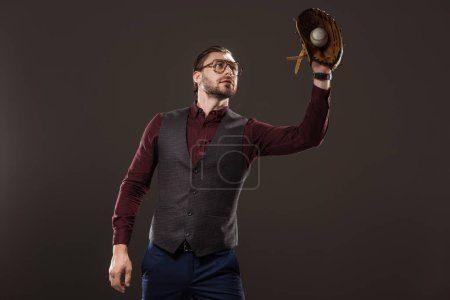 concentrated businessman in eyeglasses catching baseball ball with glove isolated on black