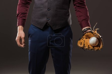 cropped hot of businessman with baseball glove holding ball isolated on black