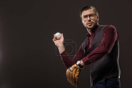 serious businessman in eyeglasses playing baseball isolated on black